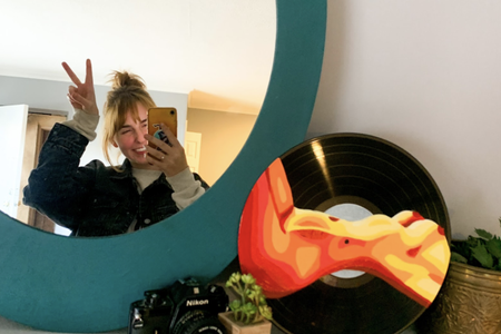 Artist Maggie Phipps poses in the mirror with one of her pieces