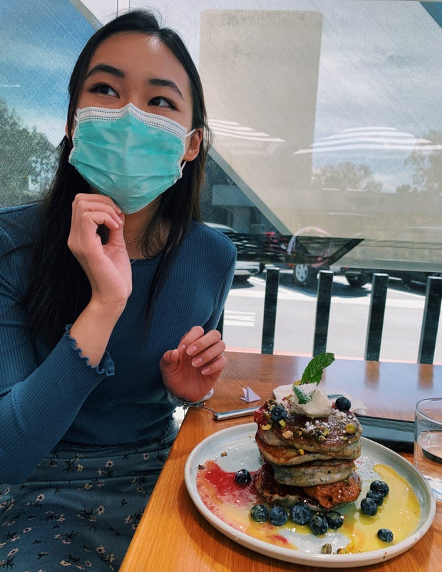 Girl in a mask and blue top is looking away from the camera while there is a stack of pancakes next to her on the table
