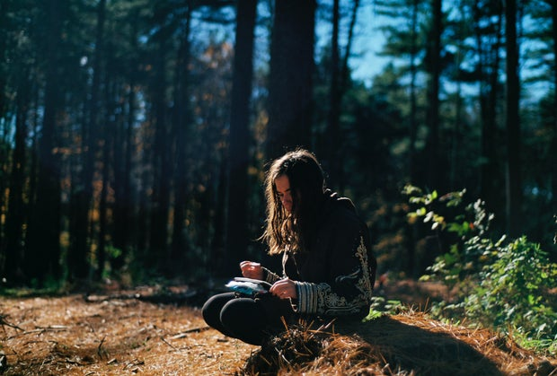 woman sitting in the forest writing