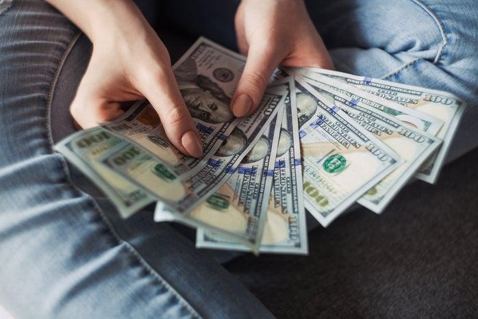 person holding $100 Dollar bills