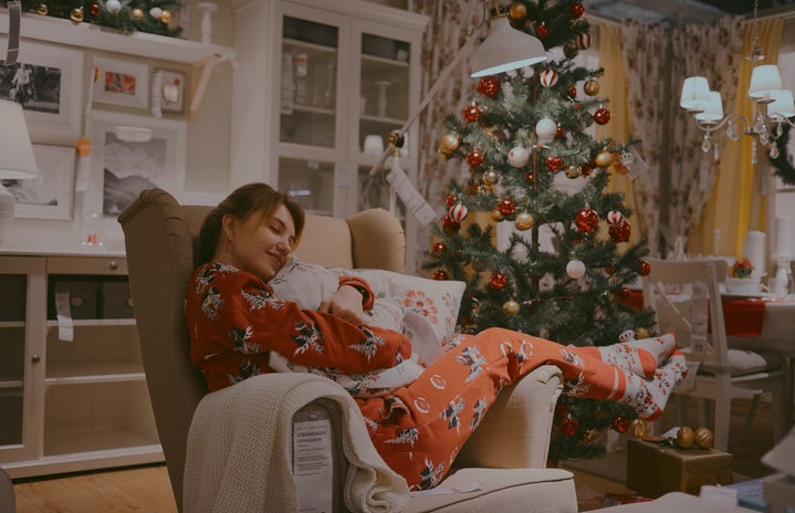 woman in pajamas hugging a pillow with christmas tree in background
