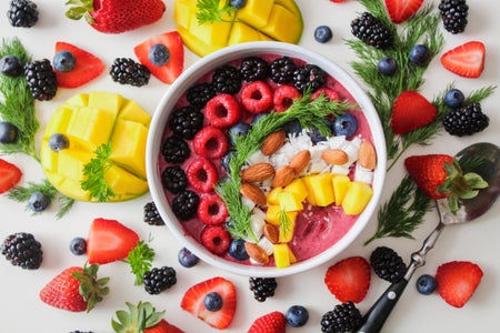 Pretty smoothie bowl surrounded by fruit.