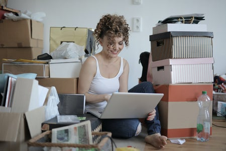 woman sitting on the floor among some boxes in a messy room