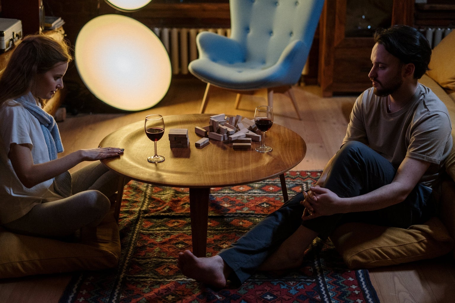 man and woman playing jenga on wooden floor table with wine