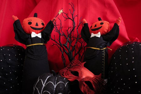 2 pumpkin figures in black with black accessories and red background