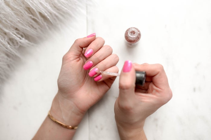 Girl painting her nails pink