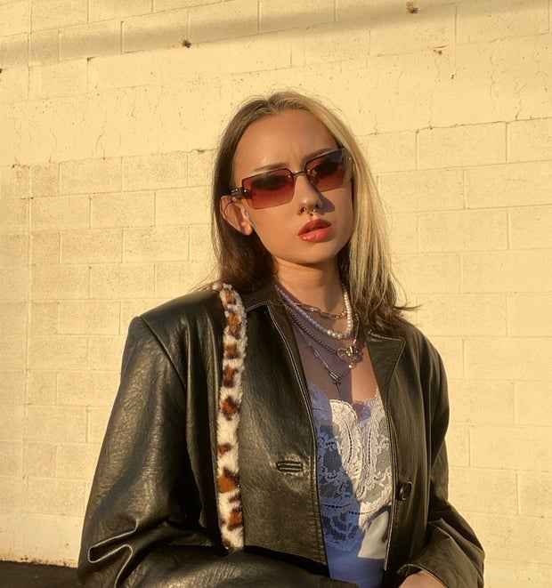 Woman in leather jacket standing in front of brick wall