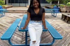 Young Black woman, Sheila Hodges, leaning against an aqua blue table and wearing a black top, white jeans with a belt, and sandals.