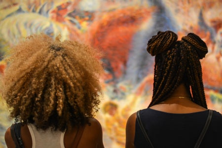 Two black women with different natural hairstyles looking at art