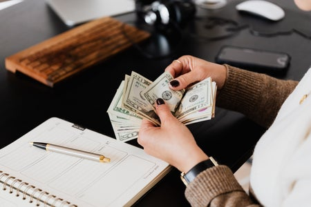 woman counting money near notebook on desk