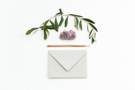 envelope, pencil, crystal, and plant on top of white surface