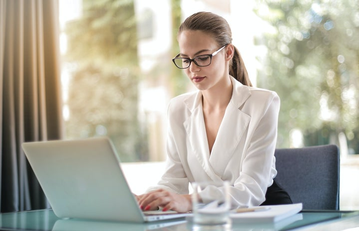 Woman with glasses and hair up sits in front of a window with her laptop in front of her.