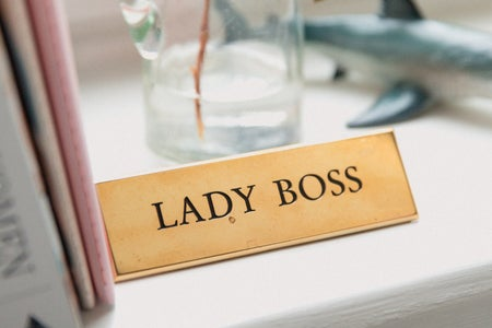 "minimalist desk space with a pink folder and a plant. a gold plaque reads ""lady boss"""