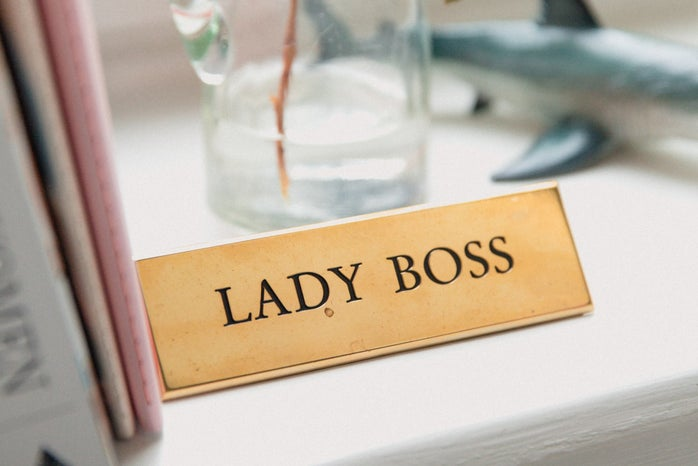 """minimalist desk space with a pink folder and a plant. a gold plaque reads """"lady boss"""""""