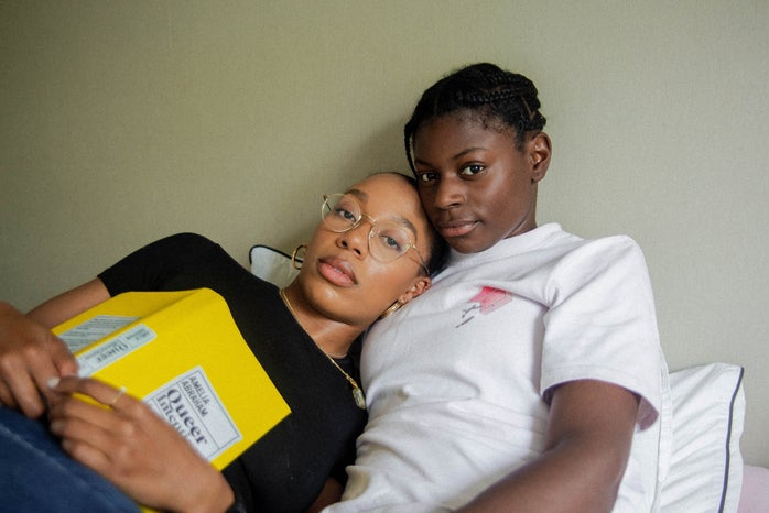 queer couple reading in bed