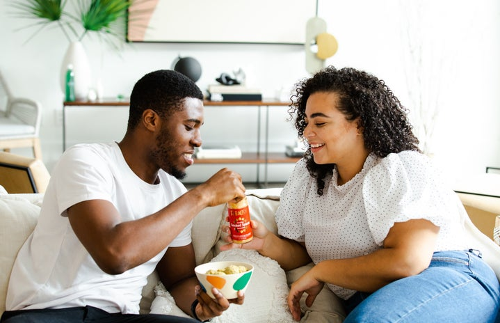 couple snacking on couch