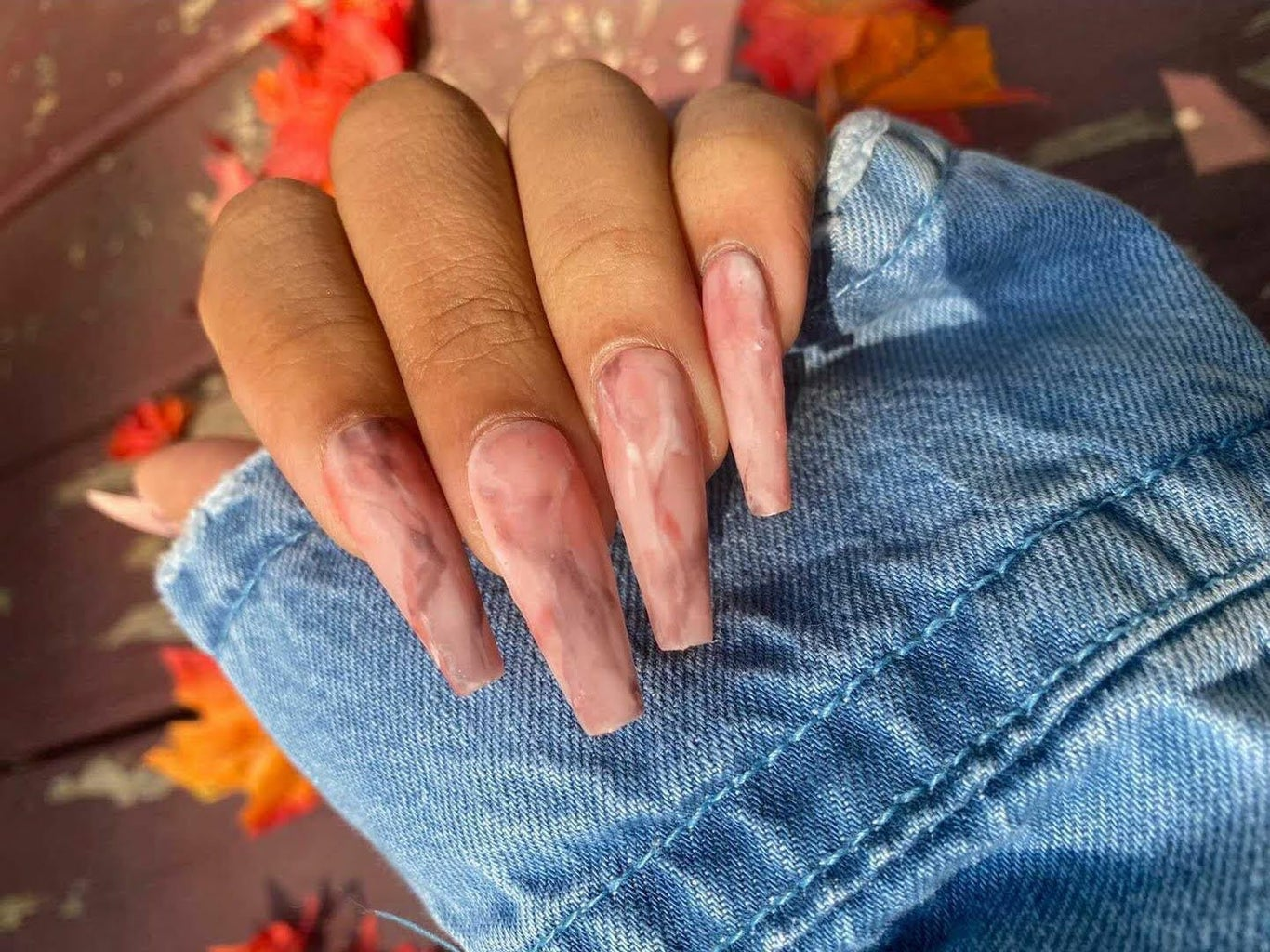 close up of hand with light pink, red, and white mixed acrylic nails