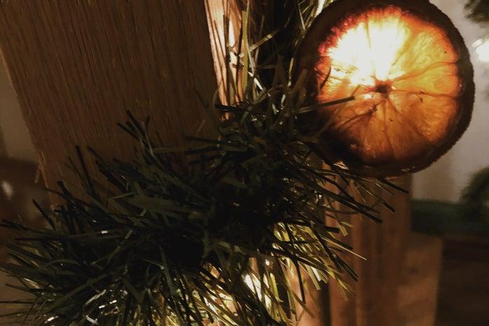 Orange Christmas garland strung around staircase with lights that illiumate the garland