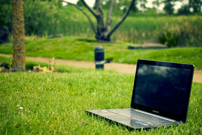 gray and black laptop sitting on the grass