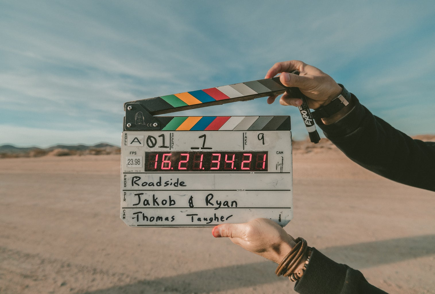 """colorful \""""action\"""" sign being held up by the hand of a director in the center of a desert"""