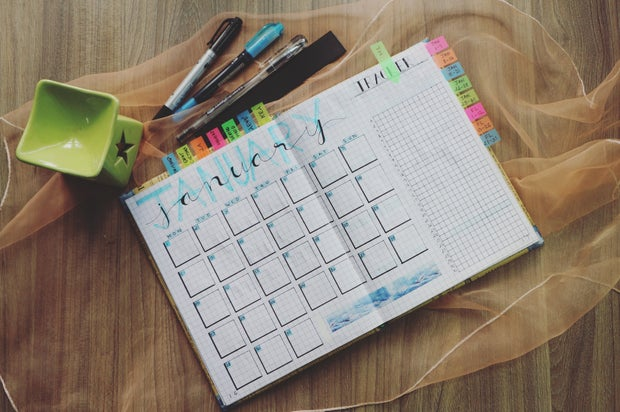 A planner and pens sit on table