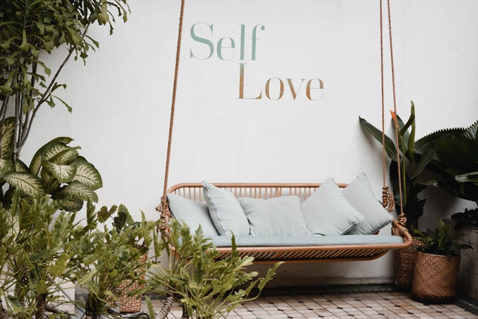 A swing in front of a spa in Bali that says self-love on the wall behind it