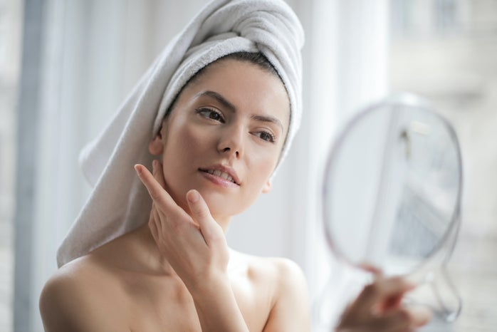 woman with towel on her head looking at herself in the mirror, clear skin