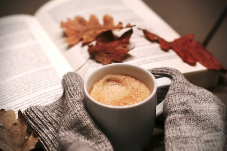 A coffee mug, leaves, and a book