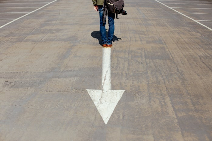 person standing on arrow sign on road photo