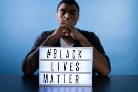 man behind a black lives matter sign