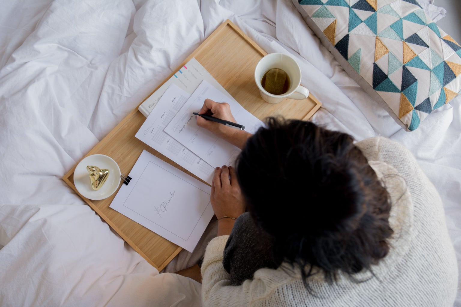 A girl si in a bed writing and drinking coffee