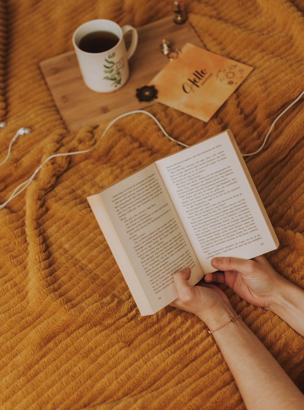 Someone holding a book on a yellow bed.