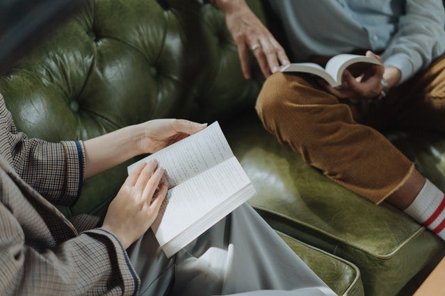 two people reading books on couch
