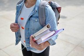 woman wearing blue denim jacket holding book.