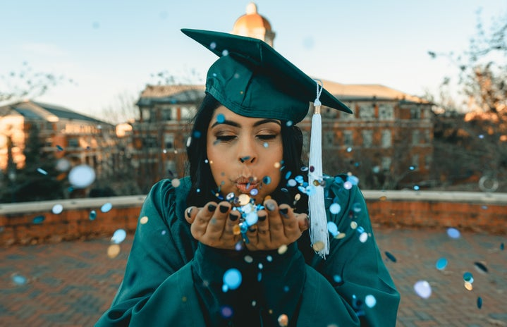 woman in green graduation gown blowing confetti
