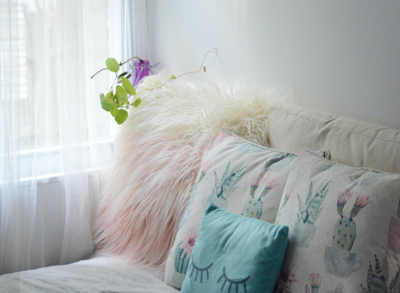 pink and white fluffy pillows on a white bed