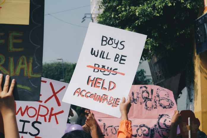 """a sign at a protest with the phrase \""""boys will be (boys) held accountable\"""""""
