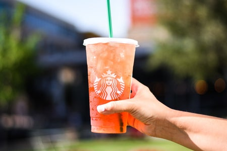 Hand holding pink Starbucks drink outside