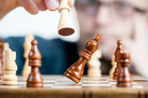Man Holding Chess Piece