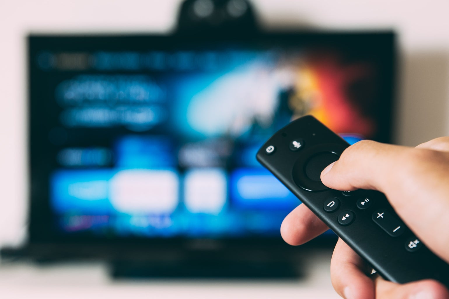 turned-on tv with hand holding remote