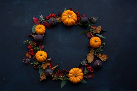 wreath with pumpkins against black background