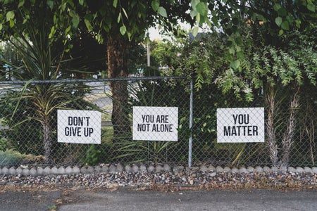 you are not alone signs along a metal fence