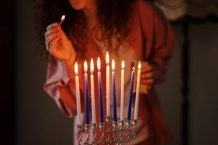 woman lighting blue and white candles on menorah