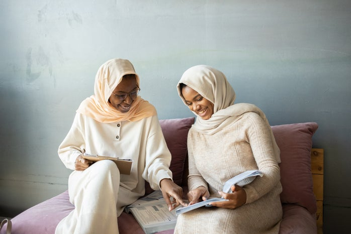 two women in hijabs reading