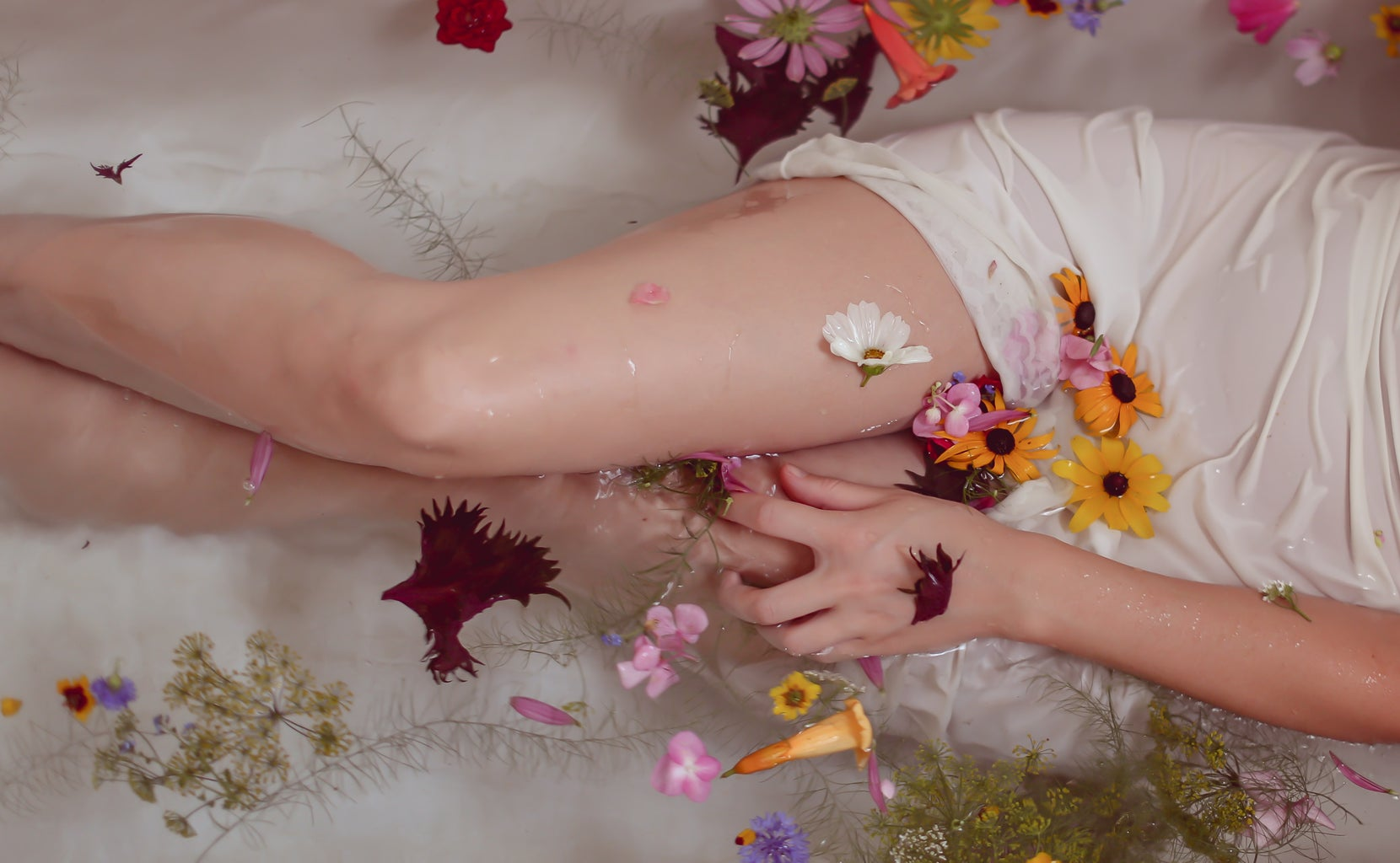 Woman in bath covered in flowers