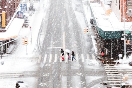 Snowy city with people walking in crosswalk