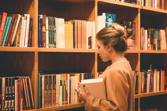 woman holding a book in front of a bookshelf