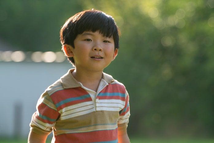 David Yi (Alan S. Kim) looking somewhere and smiling.