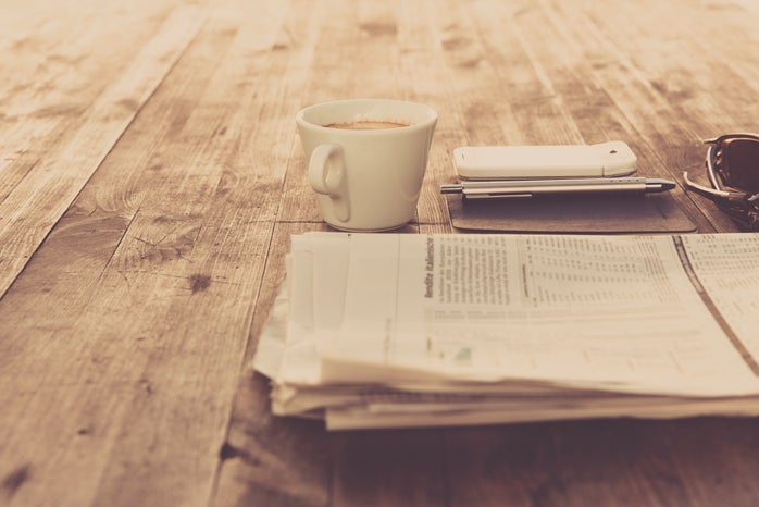A newspaper, cup with coffee, phone and a pen are laid on a wooden floor