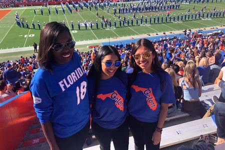 Chapter member and two friends at football game